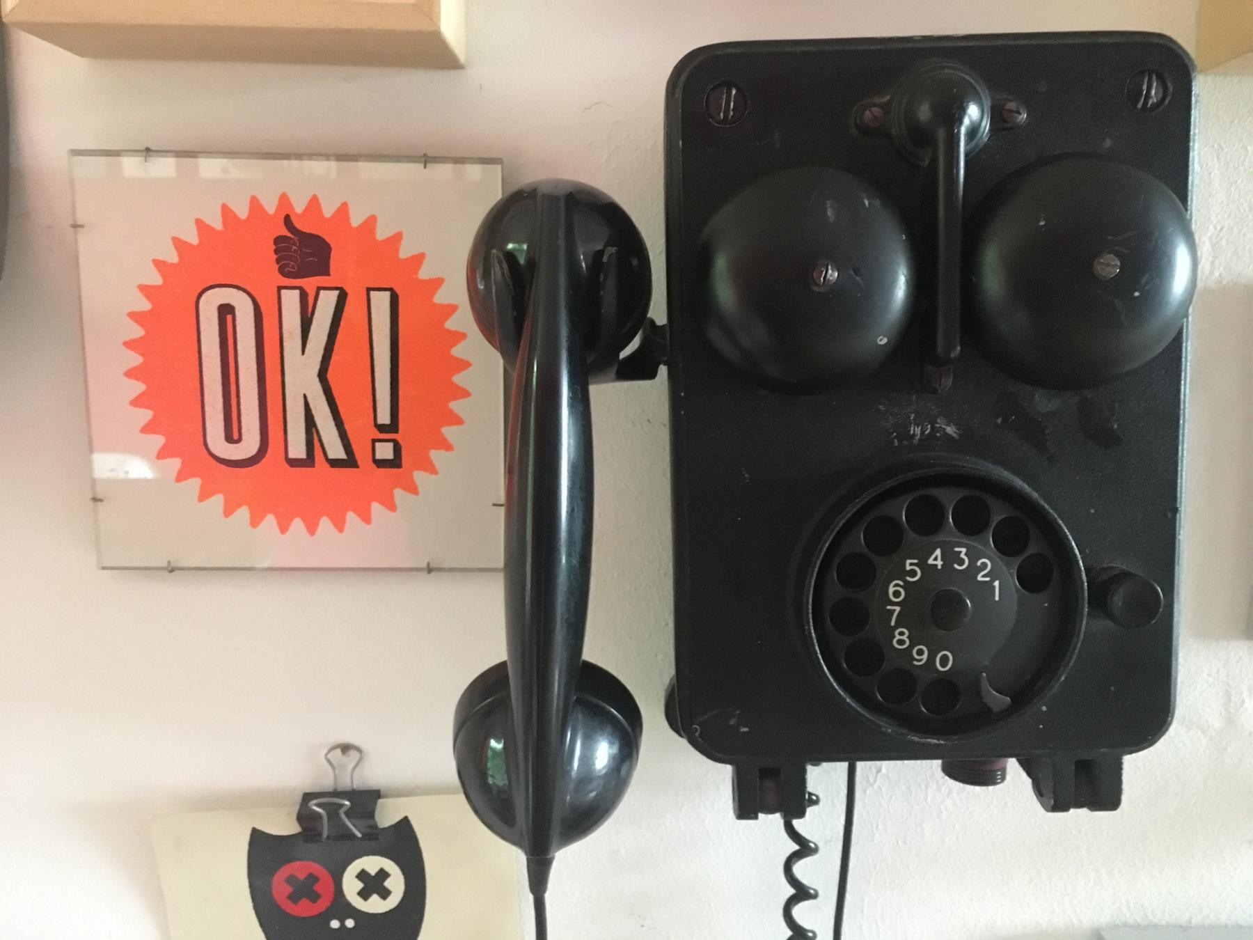 A very old industrial, black, cast iron rotary phone hanging on the wall.